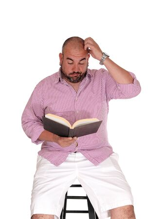 A millde age Hispanic man sitting on a chair, reading his book and scratching his head can not understand what he is reading, isolated for white background