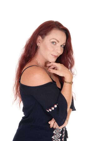 A waist up picture of a pretty woman with long red hair holding one hand under her chin smiling into the camera, isolated for white background  Stok Fotoğraf