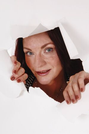 A close up image of a pretty woman peeking through a hole in a paper