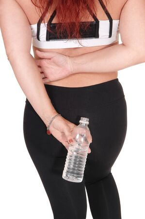 A body part image of a woman in exercise outfit standing from the  back holding a water bottle in her hand, isolated for white background
