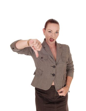 An angry businesswoman standing in a brown jacket gesturing thumpdown for not approving, isolated for white background
