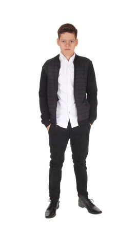 A serious looking teen boy standing with his hands in his pocket, in a  black jacket and pants, isolated for white background  Imagens