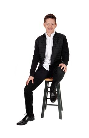 A handsome youth teen boy sitting on a chair in the studio is a black jacket and pants, smiling, isolated for white background  Imagens