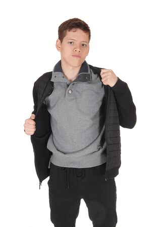 A close up image of a young teenager boy standing isolated for white  background in the studio, taking his jacket of