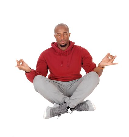 A handsome African American man sitting in a burgundy hoody on the floor doing his yoga exercise, isolated for white background
