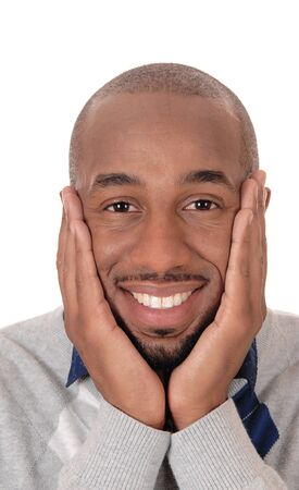 A good looking African American man in closeup, holding his face in his hands, smiling, isolated for white background