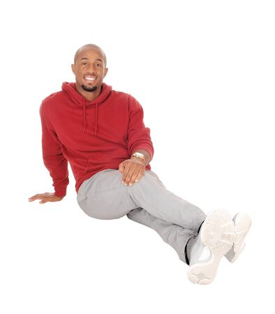 A handsome African American man sitting in a burgundy hoody on the floor resting after exercise, isolated for white background
