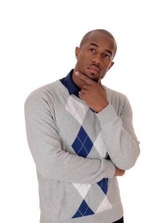 A young handsome African American man standing waist up in the studio with one hand on neck, thinking, isolated for white background