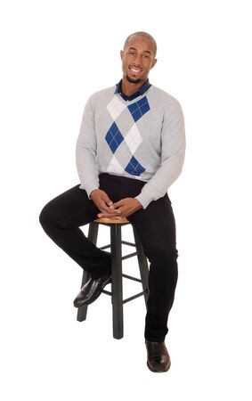 A young handsome African American man sitting full body in the studio, thinking and smiling, isolated for white background
