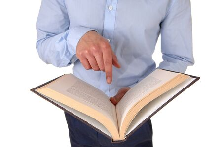A young man standing is the studio holding an open book and pointingat was he is reading, in close up, isolated for white background