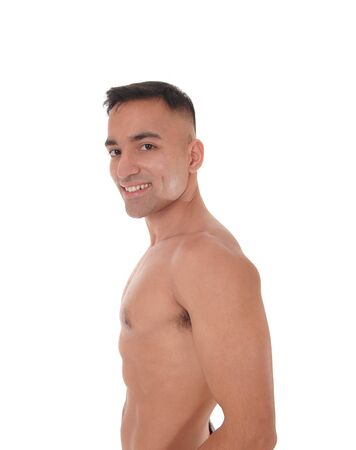 A handsome young east Indian man standing shirtless and smiling looking into the camera, isolated for white background