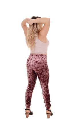 A young beautiful woman standing with her hands behind her headfrom the back in tights, isolated for white background Zdjęcie Seryjne