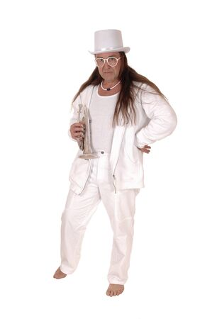 A middle age indigenous man standing in a white outfit and white hatholding his trumpet with his long hair, isolated for white background