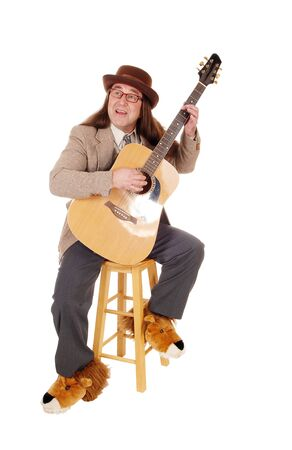 A middle age indigenous man in fancy shoes sitting and playing