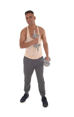 A handsome east Indian man standing in track pants working with two dumbbells, isolated for white background
