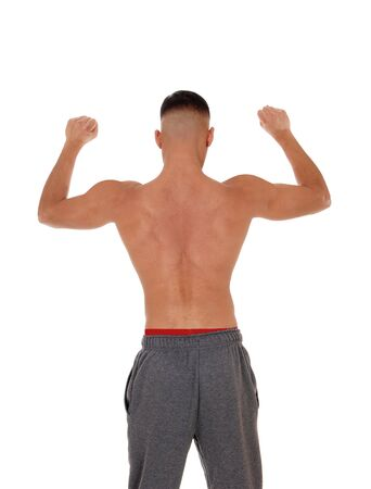 A handsome young east Indian man standing shirtless from the back in track pants with red underwear, isolated for white background