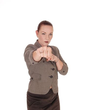 A middle age businesswoman standing and punching with her fist is very angry, isolated for white background