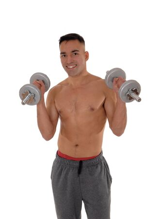 A east Indian man working out wit two dumbbells shirtless in his track pants and red underwear, isolated for white background Reklamní fotografie