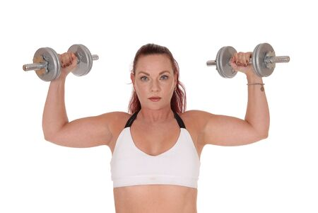 An exercising pretty woman standing in a sports bra and lifting up the two dumbbells in her hand, isolated for white background