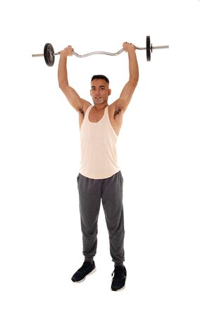 A tall young man standing in the studio in exercise outfit lifting some weight over his head, isolated for white background Reklamní fotografie