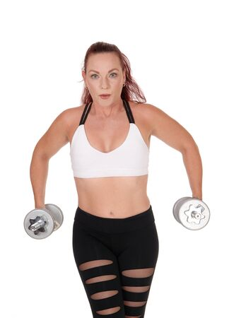 A middle age woman standing from the front lifting her two dumbbells whit her long red hair and workout outfit, isolated for white background Reklamní fotografie