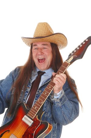 A handsome indigenous man in a jeans jacket and a cowboy hat standing and playing the guitar, isolated for white background