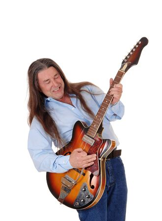A happy musician playing his guitar with his long brunette hair, singing, isolated for white background Reklamní fotografie
