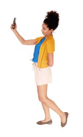 Beautiful young multi-racial woman standing in shorts and a yellow