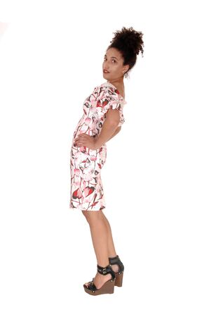 A full body image of a multi-racial woman standing in profile in summerdress with her hands on her hip, with a slim figure and curly blackhair, isolated for white background