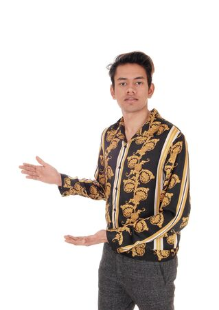 A tall young man standing in a gold colored shirt shoeing with his handsisolated for white background
