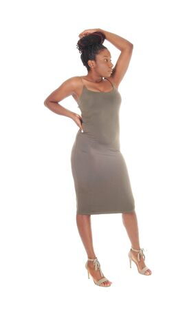 A beautiful young African American female standing in a tightgray dress, showing her figure, isolated for white background Stock fotó