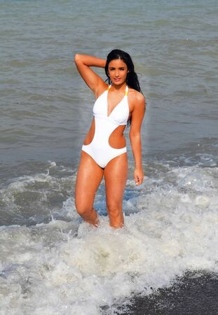 Beautiful young woman enjoying standing in a white swimsuit in the oceanin the waves, whit her long black hair Standard-Bild