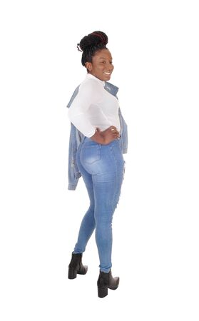 A tall young African American woman standing in jeans, from the back, jacket over her shoulder, isolated for white background 免版税图像