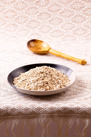 Oats flakes in a plate and with a wooden spoon