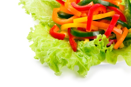 Mix of fresh vegetables from a colored paprika on leaves of green salad on a white background