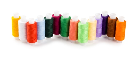 Spools multi-colored threads located a wave isolated on a white background