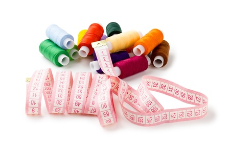 Spools Multi-colored threads randomly with a measuring tape of the tailor isolated on a white background