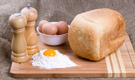 Yolk, eggs of house hens, salt, pepper and fresh hot home-made bread with wheat flour on kitchen to a board