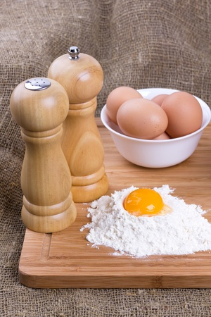 Yolk, eggs of house hens, salt and pepper with wheat flour on kitchen to a board Stock Photo