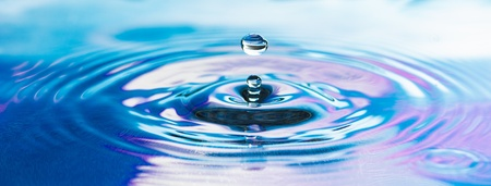 The drop of pure fresh water falls in water with splashes and vials