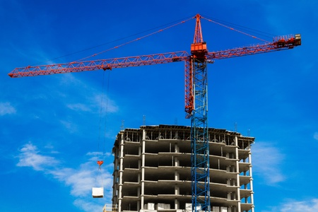 Crane and the house under construction against the blue sky with white clouds in the summer sunny day Stock Photo - 13452774