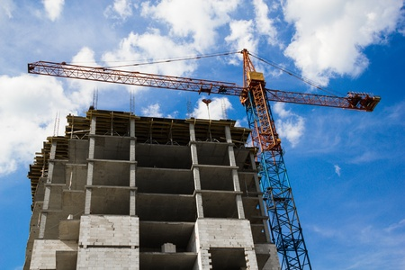 Crane and the house under construction against the blue sky with white clouds in the summer sunny day Stock Photo