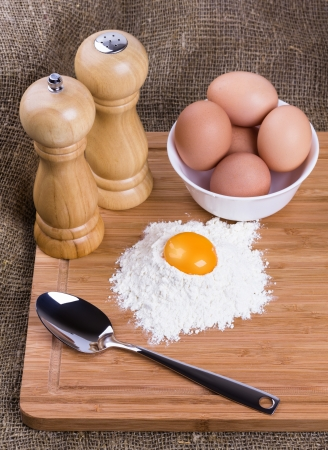 Yolk, eggs of house hens, spoon, salt and pepper with wheat flour on kitchen to a board Stock Photo - 14088401