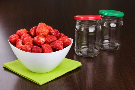 Strawberry cleared in a white bowl and empty jars with covers for house conservation