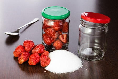 Strawberry cleared on a table with a hill of sugar and empty jars with covers for house conservation Stock Photo