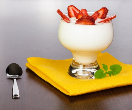 Yogurt with strawberry slices in a kremanka on a yellow napkin with a spoon, located on a brown table with a wood structure