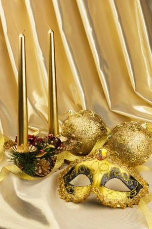 Gold mask and New Years Christmas-tree decorations with candles on yellow fabric