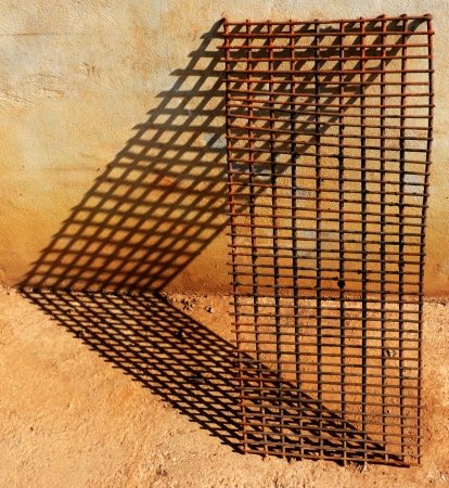 grates: Old rusty grilling grate leans against a wall with shadows on the ground and on the wall in the shape of small rectangles