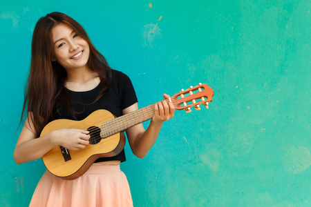 A beautiful girl is playing guitar happily in front of a blue background