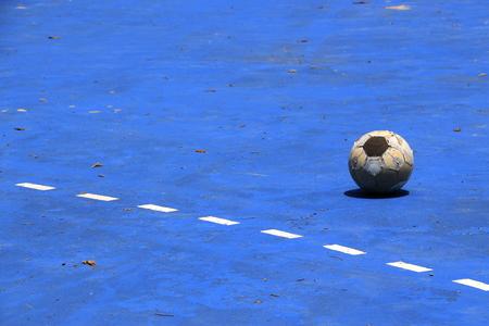 Futsal ball on blue background field photo